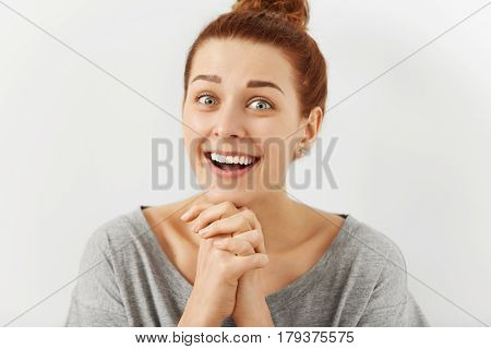 Funny Emotional Young Redhead Woman With Hairbun Keeping Hands Clasped As If Trying To Be Nice, Flat