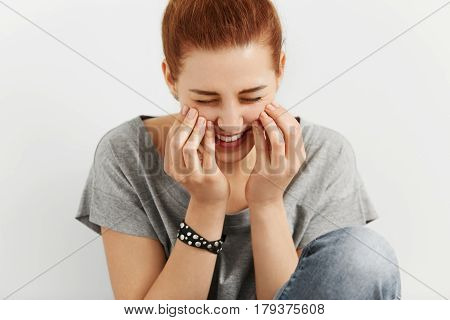 Close Up View Of Shy Caucasian College Student Touching Her Cheeks With Both Hands Looking Happy And