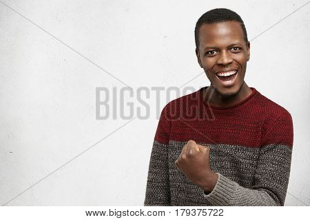 Happy Successful Lucky Young Dark-skinned Man In Warm Sweater Smiling Joyfully, Cheering, Feeling Ex