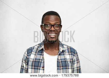 Portrait Of Happy Bug-eyed Young African College Student In Black Glasses Looking At Camera With Wid