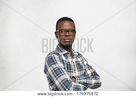 Arrogant Afro-american Young Hipster Wearing Glasses In Black Frame And Checkered Shirt Looking At C