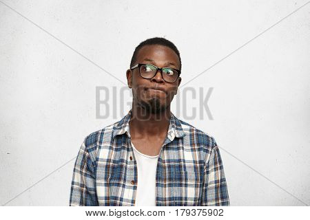 I Don't Know. Clueless Funny Young Dark-skinned Male Wearing Stylish Glasses Pursuing Lips And Looki