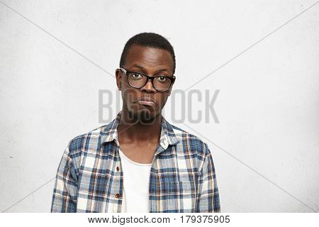 Sad Young Afro-american Man In Trendy Shirt And Eyeglasses Screwing Up Lips While Feeling Disappoint