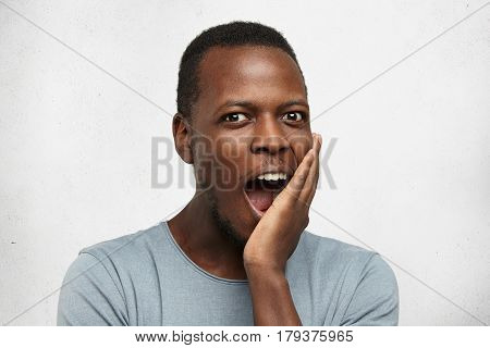 Happy Excited Young Afro-american Man In Grey T-shirt Opening Mouth In Amazement, Touching His Face