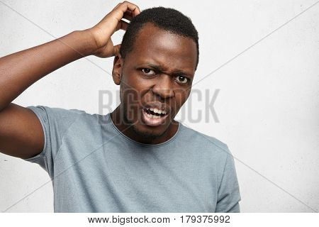 Headshot Of Clueless Perplexed Young African American Man In Grey T-shirt Looking At Camera With Con
