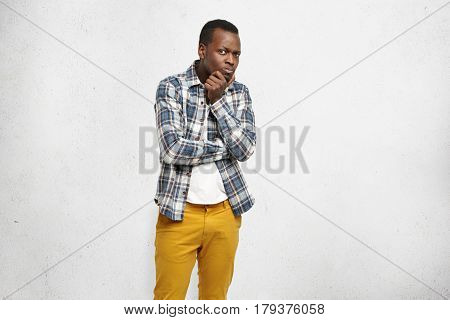 Distrustful Black Man Wearing Stylish Clothing Keeping Arms Folded, Touching His Chin, Looking At Ca