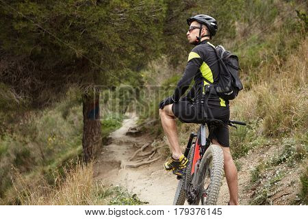Cropped Shot Of Stylish Professional Biker In Sportswear, Helmet And Eyeglasses Resting In The Middl