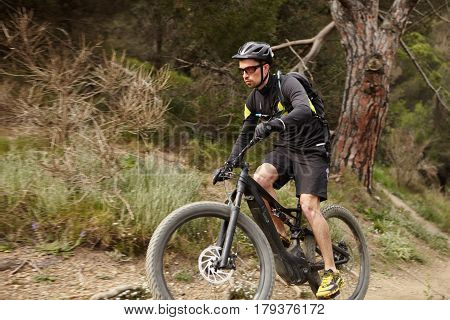 Handosme Confident Male Cyclist In Protective Gear Riding Black Electric Motor-powered Bicycle With