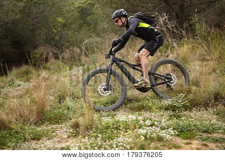 Young Rider Cycling On Pedelec In Forest, Making Mountain Biking Stunts. Outdoor Shot Of Risky Coura