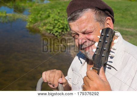 Portrait of Ukrainian senior squinted sitting on a riverside in light shirt and holding walking stick and mandolin