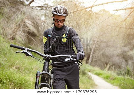 Handsome Unshaven Young European Cyclist In Helmet And Glasses Messaging Friends On Mobile Phone Aft