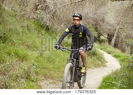 Outdoor Portrait Of Tired Young Professional Rider With Stubble Riding Electric Bike Along Trail In