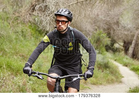 Serious Handsome Male Biker Wearing Black Sports Clothing, Helmet And Eyeglasses Speeding On Motor-p