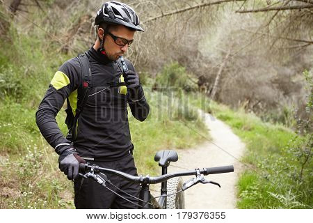 Outdoor Portrait Of Handsome Professional Rider In Cycling Clothing Holding Handlebar Of Black Motor