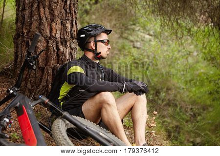 Cyclist Sitting On Ground At Big Tree In Forest Near His Motor-powered Electric Bicycle Waiting For