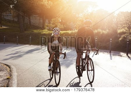 Family Of Professional Riders Cycling On Racing Bikes On Highway On Sunday Morning. Athletic Couple