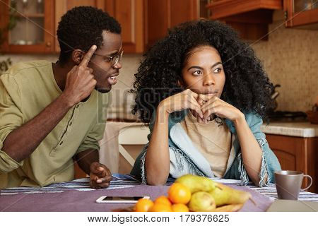 Couple Having Dispute. Annoyed Beautiful Dark-skinned Female Sitting At Kitchen Table, Ignoring Scre