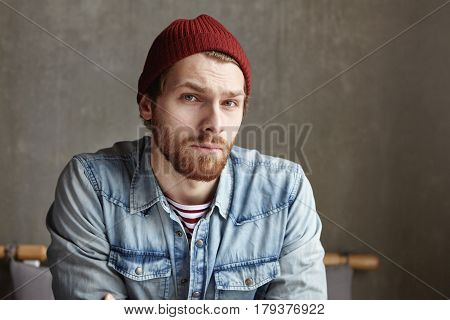 Headshot Of Macho Hipster With Stylish Beard Wearing Hat And Jeans Shirt Looking At Camera With Doub