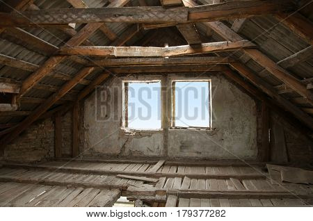 The process of building reconstruction. An old attic loft with a wooden roof broken floors and brick walls.