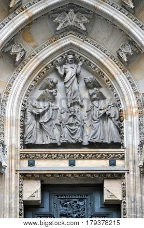 Detail of the main entrance of the Gothic Church of St. Vitus in Prague. Gates decorated with religious sculpture made of stone.
