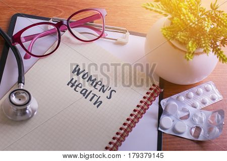 Stethoscope On Note Book With Women's Health Words As Medical Concept.