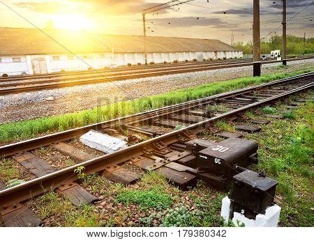 Green grass near rails along industrial station