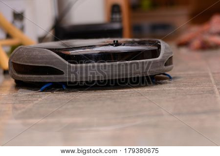 Vacuum cleaner robot cleans smooth surface - close-up