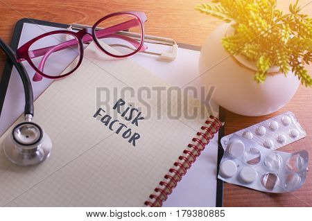 Stethoscope On Note Book With Risk Factor Words As Medical Concept.
