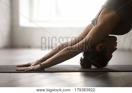 Young attractive woman practicing yoga, standing in Downward facing dog exercise, adho mukha svanasana pose, working out, wearing sportswear bra, white loft studio background, close up