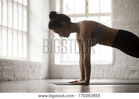Young attractive woman practicing yoga, standing in Push ups or press ups exercise, Plank pose, working out, wearing sportswear, white loft studio background, side view, close up