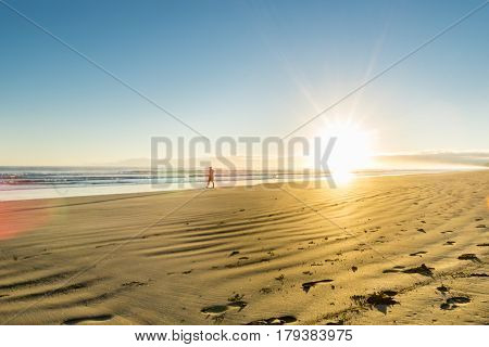 Golden beach huer at sunrise over wide flat sandy beach at Ohope Whakatane New Zealand with distant silhouette of man walking