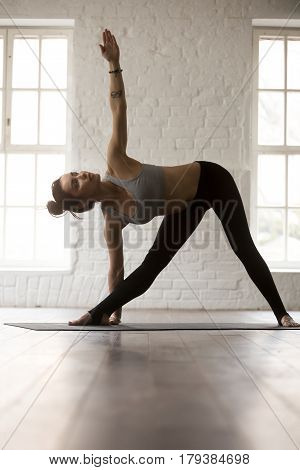 Young attractive yogi woman practicing yoga concept, standing in Utthita Trikonasana exercise, extended triangle pose, working out, full length, white loft studio background, vertical, copy space