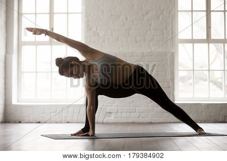 Young attractive yogi woman practicing yoga concept, standing in Utthita parsvakonasana exercise, Side Angle pose, working out, wearing sportswear, full length, white loft studio background, closeup