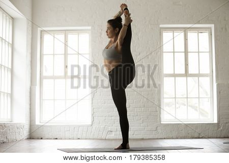 Young yogi woman practicing yoga concept, Variation of Utthita Hasta Padangushthasana pose, Trivikramasana, standing splits, working out, wearing sportswear, full length, white loft studio background
