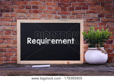 Requirement word on blackboard with green plant poster