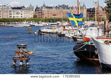 Stockholm Sweden - August 30 2016: Stockholm waterfront at Nybroviken seen from the Skeppsholmen bridge with boats and buildings at the street Strandvagen in the background.