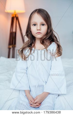 Cute little girl wearing nightgown sitting on the bed in bedroom, childhood concept, indoor vertical portrait.