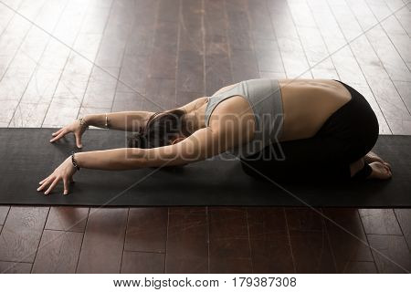 Young attractive sporty yogi woman practicing yoga concept, sitting in Child exercise, Balasana pose, working out wearing sportswear, full length, wooden floor, studio background. high angle back view