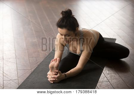 Young yogi woman practicing yoga concept, sitting in Janu Sirsasana exercise, Head to Knee Forward Bend pose, working out on black mat, wearing sportswear, studio floor background, high angle view