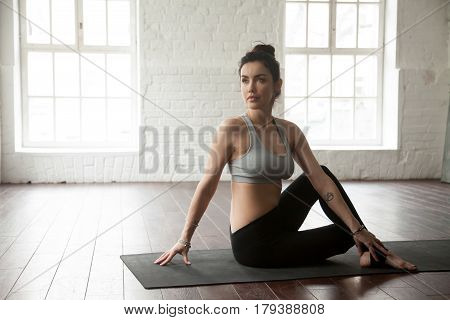 Young attractive yogi woman practicing yoga concept, sitting in Ardha Matsyendrasana exercise, Half lord of the fishes pose, working out, wearing sportswear, full length, white loft studio background