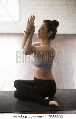 Young attractive yogi woman practicing yoga concept, sitting in variation of Gomukasana exercise, Cow Face pose, working out, wearing sportswear, full length, white loft studio background, vertical
