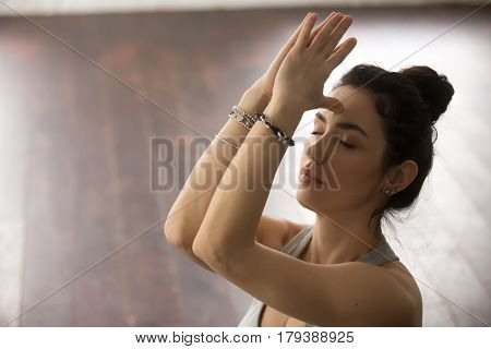 Young beautiful sporty yogi woman practicing yoga concept, doing namaste gesture, her eyes closed, namaste hands to forehead, working out, meditating, breathing, studio background