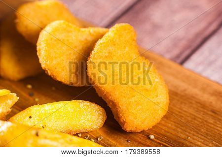 Breaded Fried Chicken Nuggets And Potatoes On Cutting Board And Rustic Wooden Background