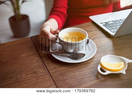 Close up of woman hand holding cup of tea with lemon, drinking tea and looking for information on Internet. Enjoying free time. Relaxing and resting concept. Chatting with friends.