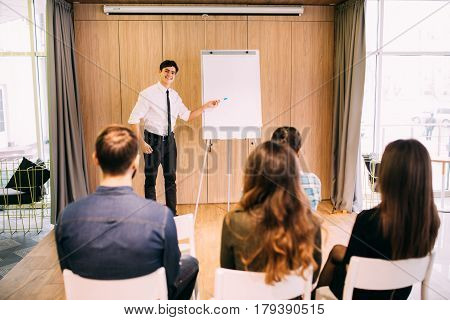 Man Present At White Copy Space Flipchart For Young People In Casual Close