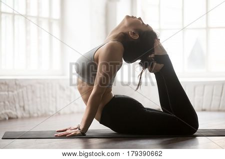 Young yogi woman practicing yoga concept, doing King Cobra exercise, Raja bhudjangasana pose, working out wearing black sportswear, full length silhouette on white loft studio background. Side view