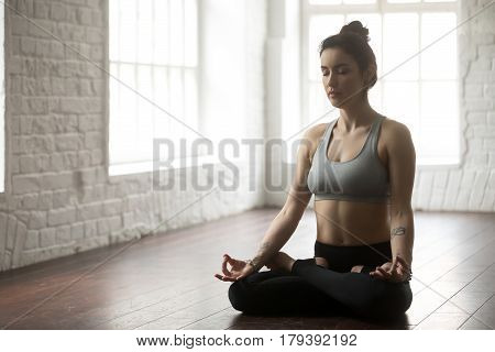 Young attractive yogi woman practicing yoga concept, sitting in Padmasana exercise, Lotus pose with mudra, working out wearing sportswear grey top and black pants, full length, loft studio background