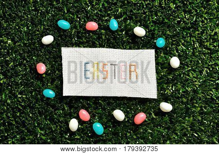 Easter cross stitched on textile isolated on artificial grass displayed with jelly beans