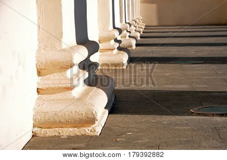 White classical column bases with contrasting shadows in perspective. Architectural geometric composition.