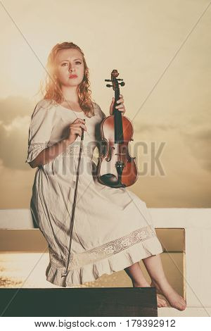 Music love hobby and everyday passion concept. Woman on pier outside holding violin during sunset